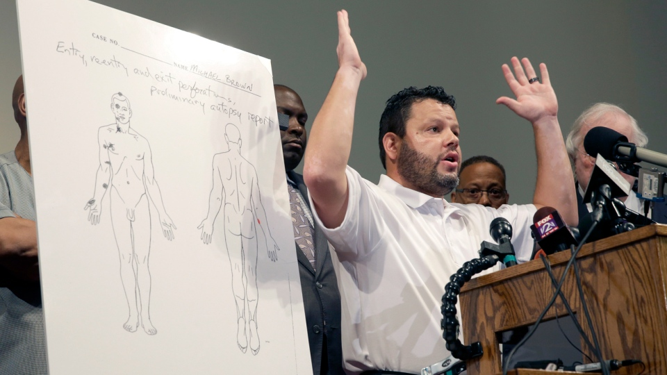 Forensic pathologist Shawn Parcells speaks during a news conference to share preliminary results of an autopsy on Michael Brown in St. Louis County, Mo., Monday, Aug. 18, 2014. (AP Photo/Jeff Roberson)