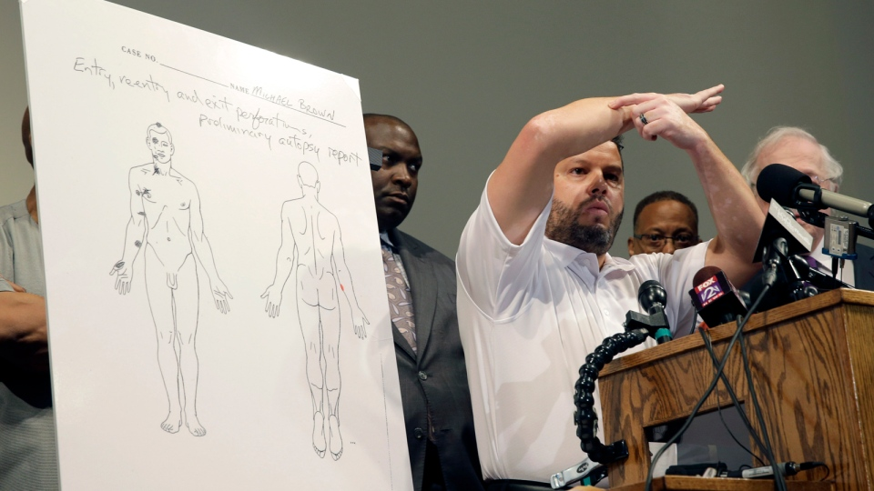 Forensic pathologist Shawn Parcells speaks during a news conference to share preliminary results of a second autopsy on Michael Brown in St. Louis County, Mo., Monday, Aug. 18, 2014. (AP / Jeff Roberson)