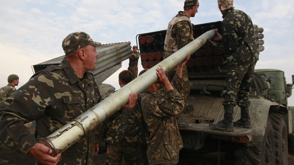 Ukrainian soldiers load a Grad missile during fighting with pro-Russian separatists close to Luhansk, eastern Ukraine, Monday, Aug. 18, 2014. (AP / Petro Zadorozhnyy)