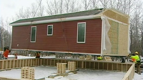 Construction workers lower a temporary mobile home into position in St. Laurent, Man.