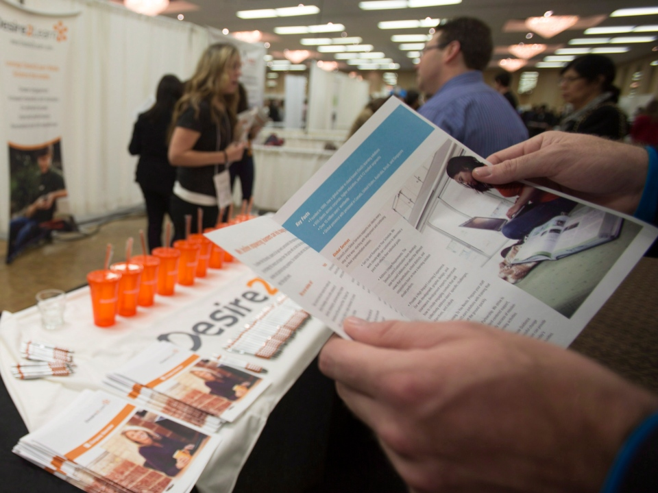 A job seeker looks at a brochure for the Kitchener-based software firm Desire2Learn at the Communitech Tech jobs + recruitment event in Kitchener on Wednesday, Nov. 13, 2013. (Geoff Robins / The Canadian Press)