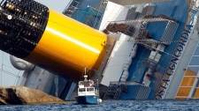 A police boat sails by the grounded cruise ship Costa Concordia, off the Tuscan island of Giglio, Italy, Sunday, Jan. 22, 2012.