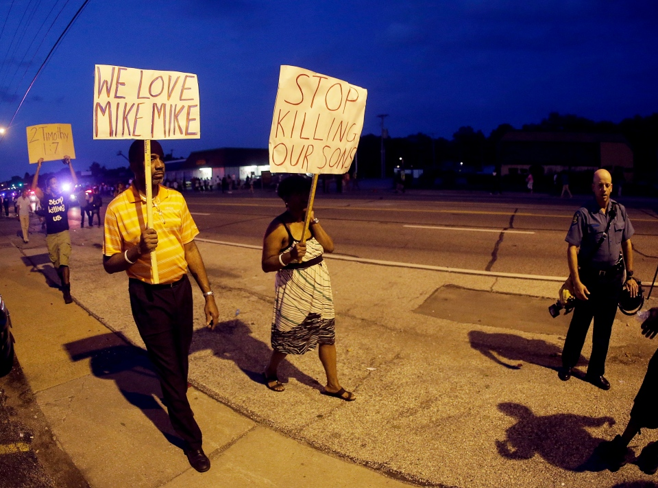 People march Monday, Aug. 18, 2014, during a protest for Michael Brown, who was killed by a police officer Aug. 9 in Ferguson, Mo. (AP / Charlie Riedel)