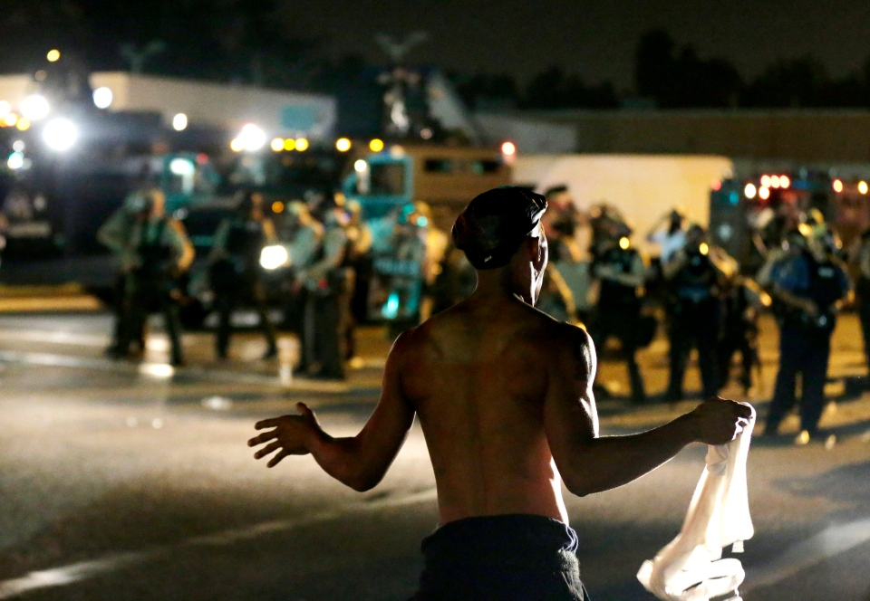 A man stands in front of police during a protest, Monday, Aug. 18, 2014. (AP / Charlie Riedel)