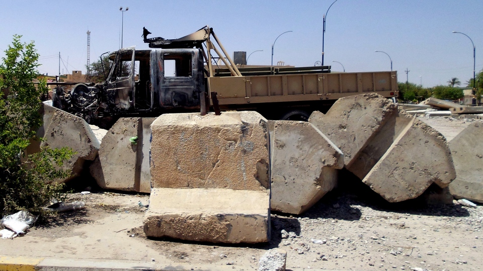 A damaged military truck after clashes between fighters of the al Qaeda-inspired Islamic State of Iraq and the Levant (ISIS) and Iraqi security forces at a military base in Tikrit, Iraq, Tuesday, July 1, 2014.  (AP)