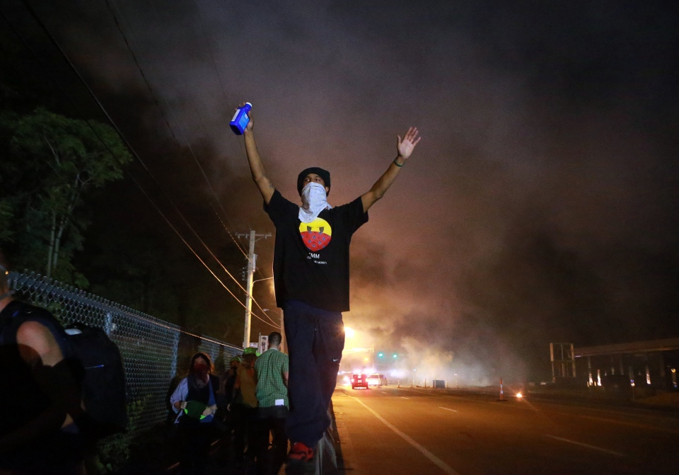 A protester raises his arms following a clash with police in Ferguson, Mo., Monday, Aug. 18, 2014. (Christian Gooden / St. Louis Post-Dispatch)