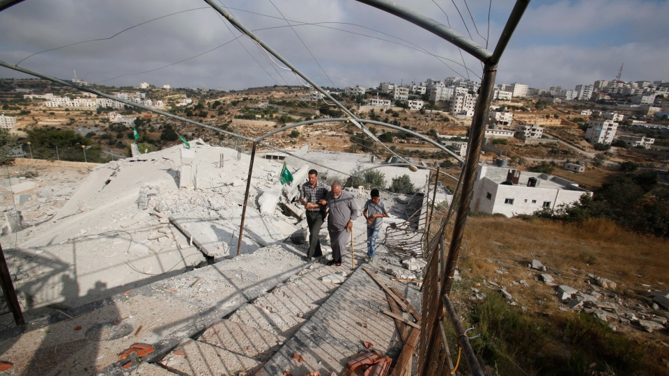 Palestinians inspect the rubble of the home of Hussam Kawasma, one of three Palestinians identified by Israel as suspects in the killing of three Israeli teenagers, after it was demolished by the Israeli army in the West Bank city of Hebron, Monday, Aug. 18 , 2014.  (AP / Nasser Shiyoukhi)