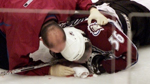 Colorado Avalanche forward Steve Moore is attended to by the team trainer after being injured in a fight with Vancouver Canucks Todd Bertuzzi in Vancouver, B.C., on March 8, 2004. (THE CANADIAN PRESS / Chuck Stoody)