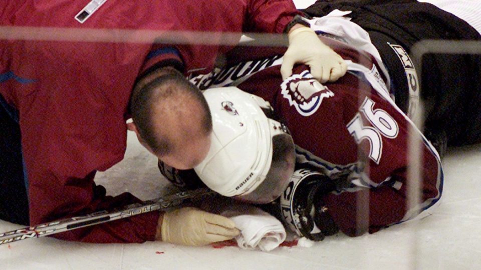 Colorado Avalanche forward Steve Moore is attended to by the team trainer after being hit by Vancouver Canucks Todd Bertuzzi in Vancouver, B.C., on March 8, 2004. (THE CANADIAN PRESS / Chuck Stoody)