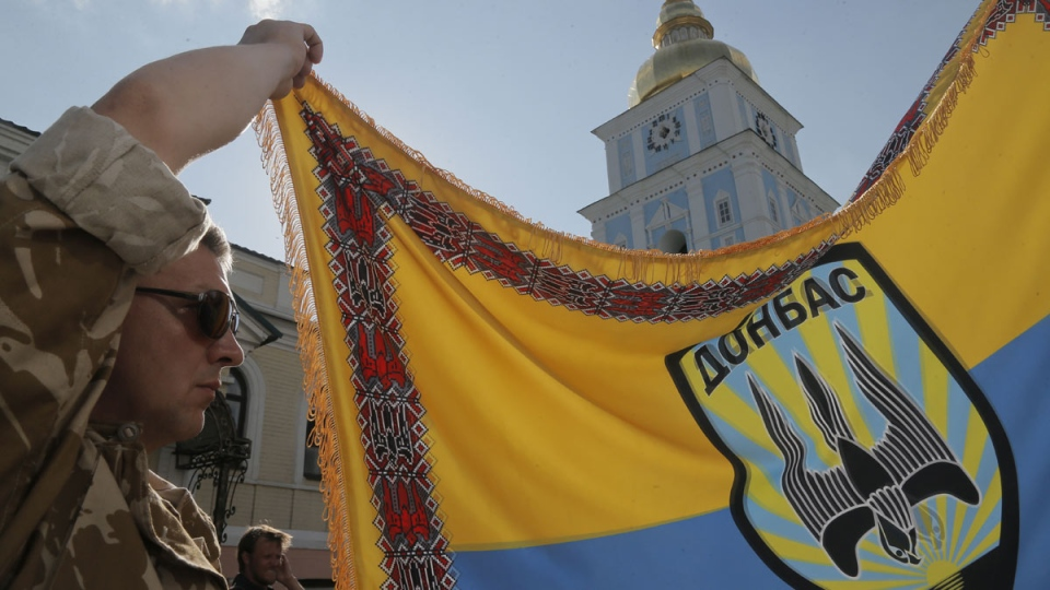 An officer of volunteer battalion 'Donbas' holds battalion colours during a blessing ceremony in St. Michael Cathedral in Kyiv, Ukraine, Tuesday, Aug. 19, 2014. (AP / Efrem Lukatsky)