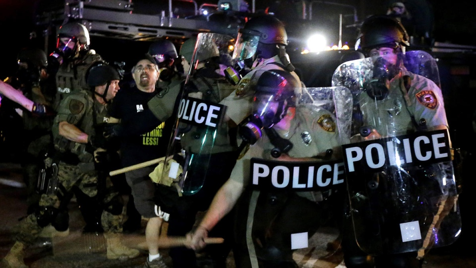 A man is detained after a standoff between protesters and police, in Ferguson, Mo.. Monday, Aug. 18, 2014. (AP / Charlie Riedel)