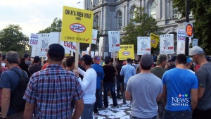 Several hundred workers demonstrate outside Montreal's City Hall Monday, Aug. 18, 2014.