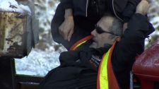 Martin Butthof is held up by a bystander after he was struck by a car and pinned against his tow truck in Richmond, B.C. Jan. 15, 2012. (CTV)