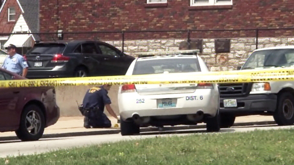 Police officials at the scene where officers shot and killed a man in St. Louis, Mo., Tuesday, Aug. 19, 2014.