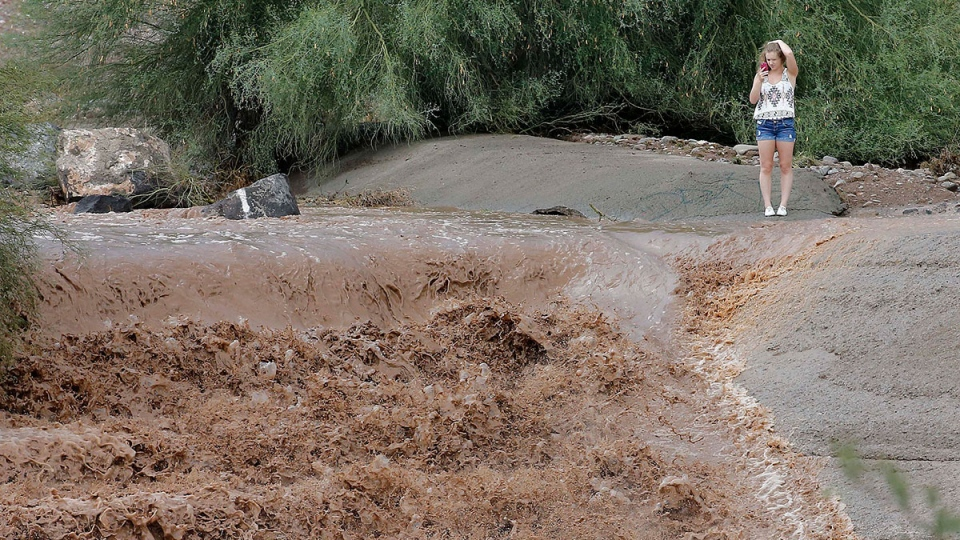 A girl photographs the flash flood waters from the Sonoran Desert overrun Skunk Creek, Tuesday, Aug. 19, 2014, in northwestern Phoenix. (AP / Matt York)
