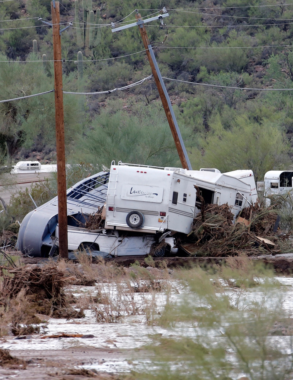 Damaged vehicles and trailers are seen in an area where flash flood waters that overran Skunk Creek, in New River, Ariz., just northwest of Phoenix, Tuesday, Aug. 19, 2014. (AP / Matt York)