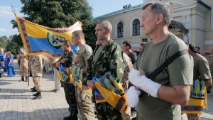 Volunteers of battalion 'Donbas' hold battalion flags during a blessing ceremony in St. Michael Cathedral in Kiev, Ukraine, Tuesday, Aug. 19, 2014. (AP / Efrem Lukatsky)