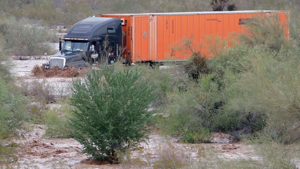 A tractor trailer drives through flash flood waters that overran Skunk Creek, Tuesday, Aug. 19, 2014, in northwestern Phoenix. (AP / Matt York)