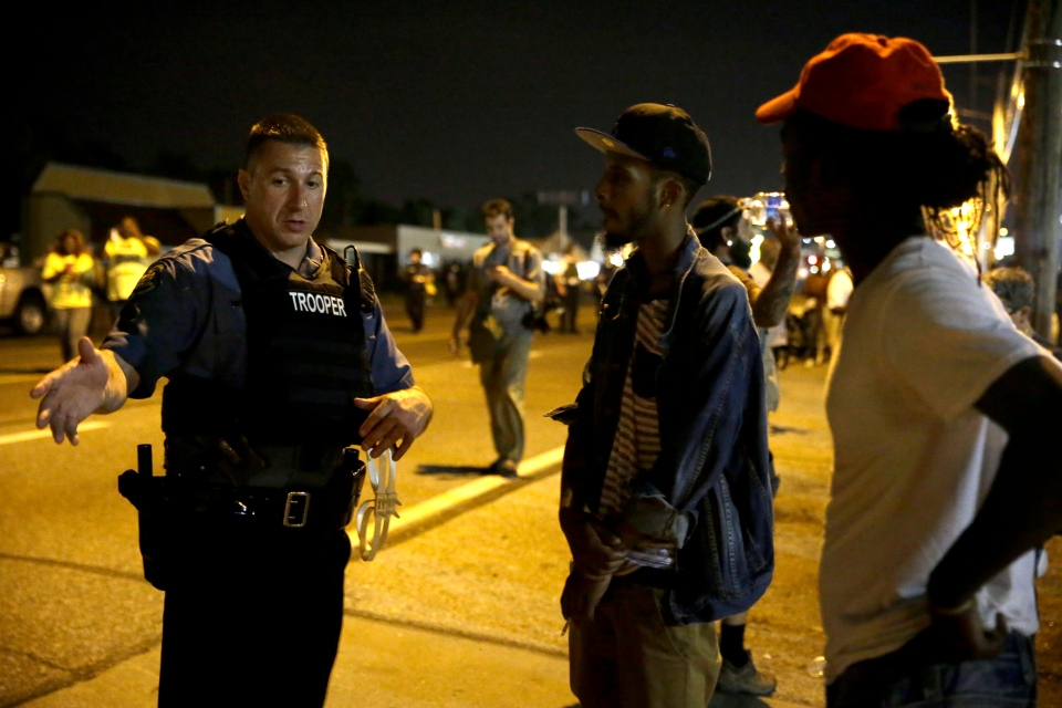 A Missouri State Trooper talks with protesters in Ferguson, Mo., early Wednesday, Aug. 20, 2014. (AP / Jeff Roberson)