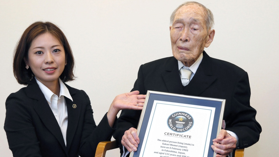 Sakari Momoi, a 111-year-old Japanese retired educator, poses for a photo after receiving a certificate from a Guinness World Records official, left, in Tokyo Wednesday, Aug. 20, 2014. (AP / Kyodo News)