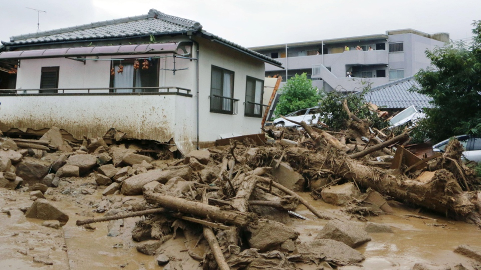 Half buried houses are seen following a massive landslides swept through residential area in Hiroshima, western Japan, Wednesday, Aug. 20, 2014. (AP / Kyodo News, Shinpei Hamaguchi)