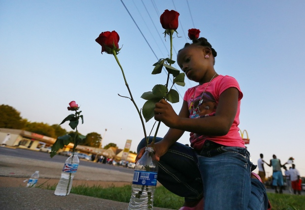 Ferguson girl with flowers for peaceful protest