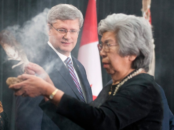 Prime Minister Stephen Harper looks on as Elder Commanda performs a smudging ceremony to open the Crown-First Nations Gathering in Ottawa, on Tuesday, Jan. 24, 2012. (Adrian Wyld / THE CANADIAN PRESS)