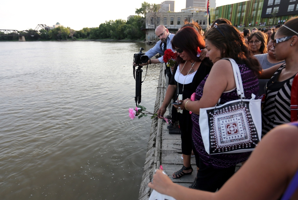 Tina Fontaine puts flowers in the river in memory of her daughter, Tina Fontaine, who was found at the Alexander Docks in Winnipeg, Manitoba on Tuesday, Aug. 19, 2014. (Trevor Hagan / THE CANADIAN PRESS)