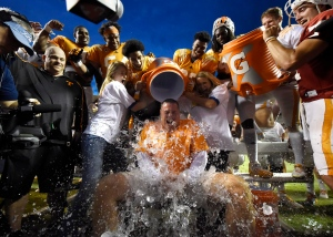 Tennessee coach Butch Jones, center, gets a cooler of ice dumped on him while participating in the Ice Bucket Challenge at the conclusion of the Tennessee football team's open practice at Neyland Stadium in Knoxville, Tenn., on Saturday, Aug. 16, 2014. (AP / Knoxville News Sentinel, Adam Lau)