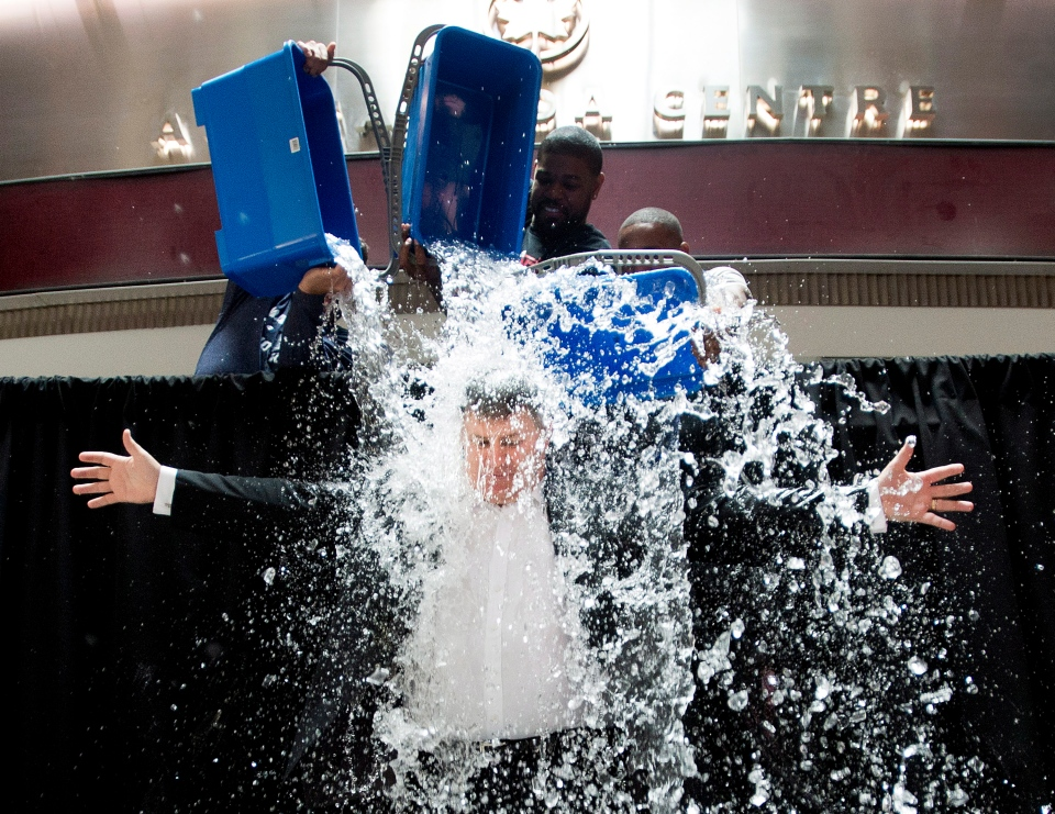 Tim Leiweke, president and CEO of Maple Leaf Sports Entertainment (MLSE), participates in the ALS Ice Bucket Challenge as Jermain Defoe, right, of Toronto FC, Nazem Kadri, left, of the Toronto Maple Leafs and Amir Johnson, centre, of the Toronto Raptors dump water on Leiweke in Toronto on Wednesday, Aug. 20, 2014. (The Canadian Press/Nathan Denette)