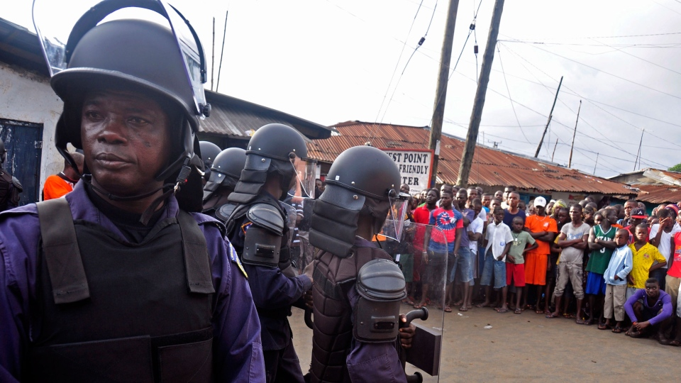 Liberia security forces dressed in riot gear, left, control a crowd of people in the West Point area, as the government clamps down on the movement of people to prevent the spread of the Ebola virus in Monrovia, Liberia, Wednesday, Aug. 20, 2014. (AP / Abbas Dulleh)