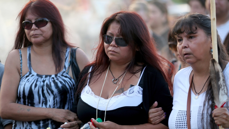 Tina Fontaine, centre, walks during a vigil honouring her daughter, Tina Fontaine, and Faron Hall at the Alexander Docks in Winnipeg, Manitoba, Tuesday, August 19, 2014. (Trevor Hagan / THE CANADIAN PRESS)