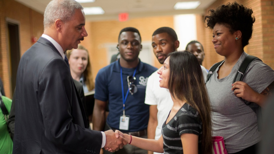 Attorney General Eric Holder shakes hands with Bri Ehsan, 25, right, following his meeting with students at St. Louis Community College Florissant Valley in Ferguson, Mo., Wednesday, Aug. 20, 2014.  (AP / Pablo Martinez Monsivais)
