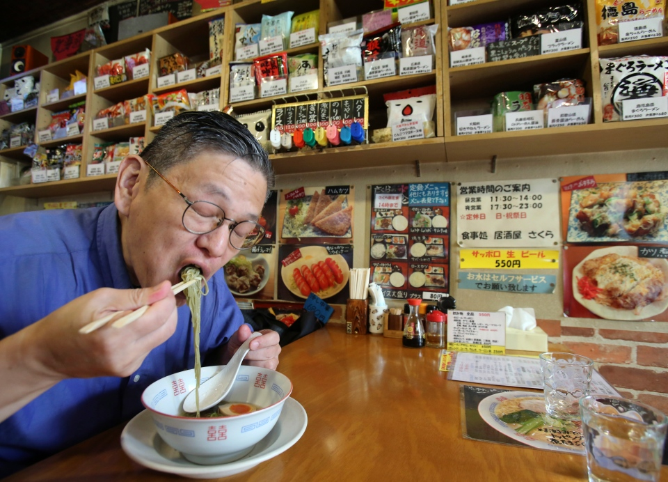 Japanese instant ramen noodle expert Masaya 'Sokusekisai' Oyama slurps noodles at a shop and restaurant specialized only in varieties of instant noodles in Tokyo on Tuesday, Aug. 19, 2014. (AP / Koji Sasahara)