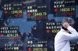 A man checks the stock prices on an electronic stock board of a securities firm in Tokyo, Aug. 19, 2014 file photo (AP / Eugene Hoshiko)