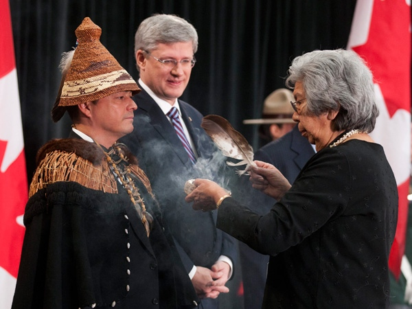 Prime Minister Stephen Harper looks on as Elder Commanda performs a smudging ceremony with Shawn Atleo, national chief of the Assembly of First Nations, to open the Crown-First Nations Gathering in Ottawa, on Tuesday, Jan. 24, 2012. (Adrian Wyld / THE CANADIAN PRESS)