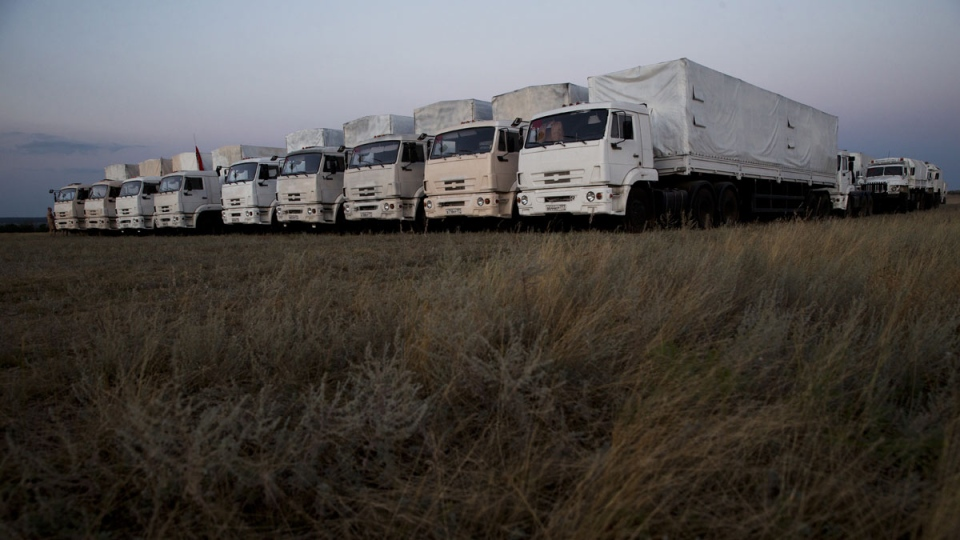 About 60 trucks forming part of a Russian aid convoy are parked in a field about 7 kilometres from a border control point with Ukraine in the Russian town of Donetsk, Rostov-on-Don region, Russia, Thursday, Aug. 21, 2014. (AP / Pavel Golovkin)