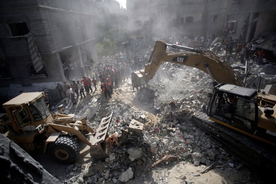 In this file photo, Palestinians gather around the rubble of a destroyed house following Israeli strikes in the Rafah refugee camp, Southern Gaza Strip, Thursday, Aug. 21, 2014. (AP Photo/Khalil Hamra)