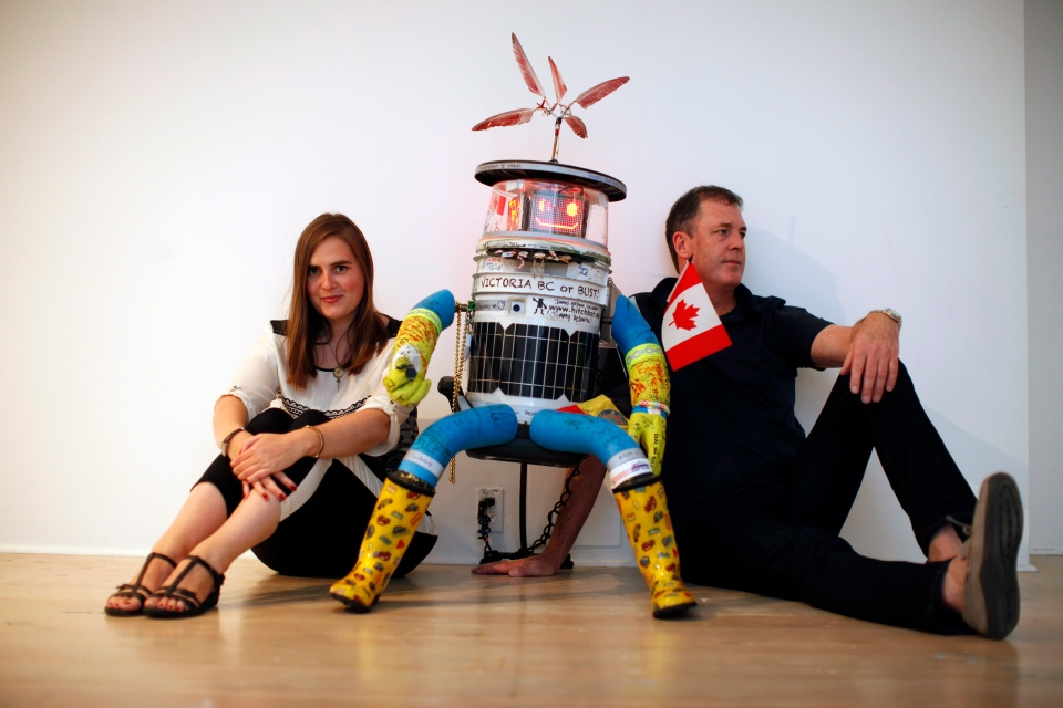 Hitchbot poses with its co-creators Frauke Zeller, an assistant professor at Ryerson University, and David Smith, a professor in the department of communication studies at McMaster University before the start of a welcome reception for Hitchbot at Open Space in Victoria, B.C., Thursday August 21, 2014. (Chad Hipolito / THE CANADIAN PRESS)