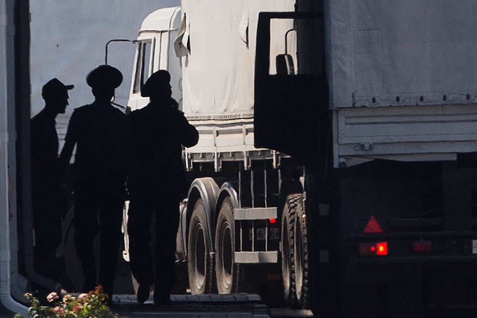 A driver, left, and Russian custom service officers stand near trucks of the Russian aid convoy, which are searched at a Russian inspection zone inside a border control point with Ukraine, in the Russian town of Donetsk on Friday, Aug. 22, 2014. (AP / Pavel Golovkin)