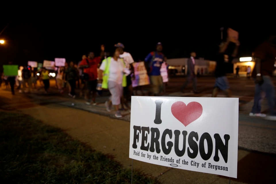 Protesters march in Ferguson, Mo., on Thursday, Aug. 21, 2014, walking in laps near the spot where Michael Brown was shot. (AP / Jeff Roberson)