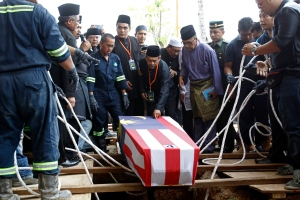 Mohamed Salleh, centre, father of Nur Shazana, a crew member who was killed in the downing of the Malaysia Airlines Flight 17, touches his daughter's coffin during a burial ceremony at Taman Selatan Muslim cemetery in Putrajaya, Malaysia on Friday, Aug. 22, 2014. (AP / Lai Seng Sin)