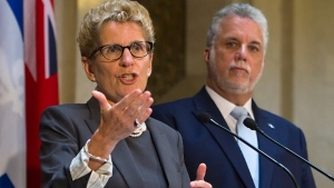 Ontario Premier Kathleen Wynne, left gestures as she responds to media after a meeting with Quebec Premier Philippe Couillard, in Quebec City, on Thursday, Aug. 21, 2014. (Clement Allard / THE CANADIAN PRESS)
