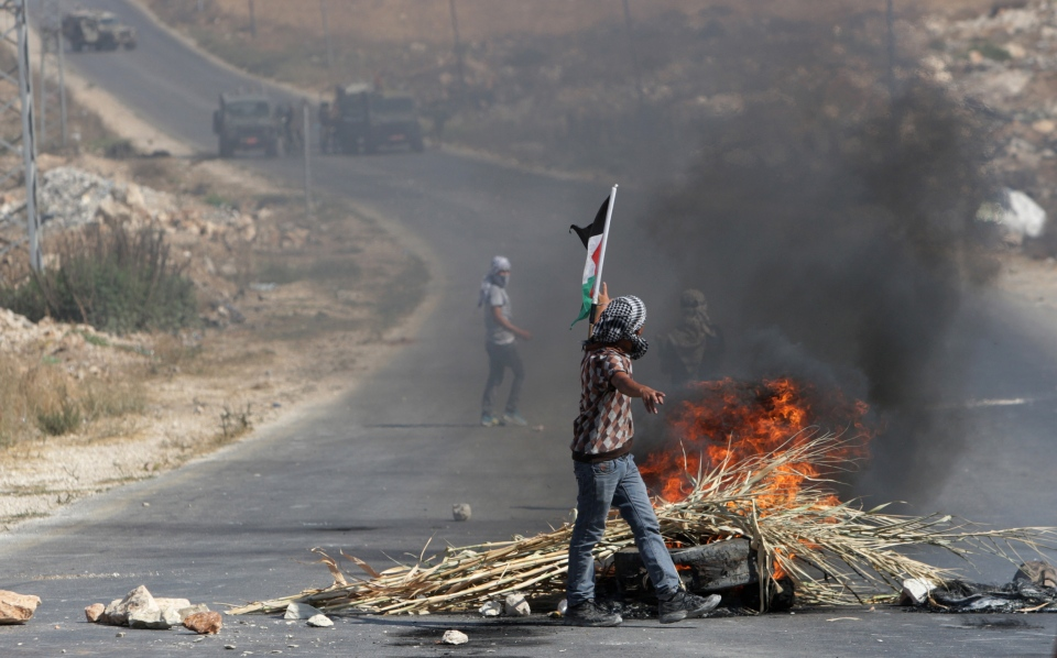Palestinian protesters face Israeli soldiers during clashes in the West Bank city of Nablus on Friday, Aug. 22, 2014. (AP / Nasser Ishtayeh)