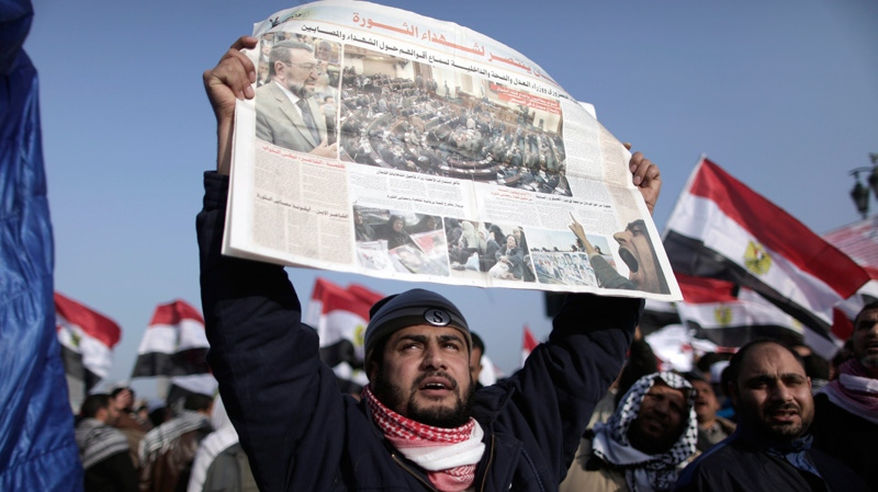 An Egyptian man holds a newspaper with a photo of the opening session of parliament as thousands gather in Tahrir Square to mark the one year anniversary of the uprising that ousted President Hosni Mubarak in Cairo, Egypt, Wednesday, Jan. 25, 2012. (AP / Muhammed Muheisen)