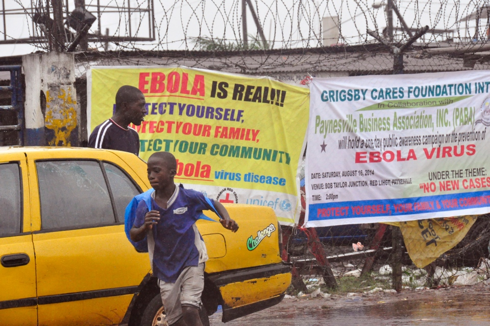 People pass by Ebola virus health warning signs, in the city of Monrovia, Liberia, Sunday, Aug. 17, 2014. (AP / Abbas Dulleh)