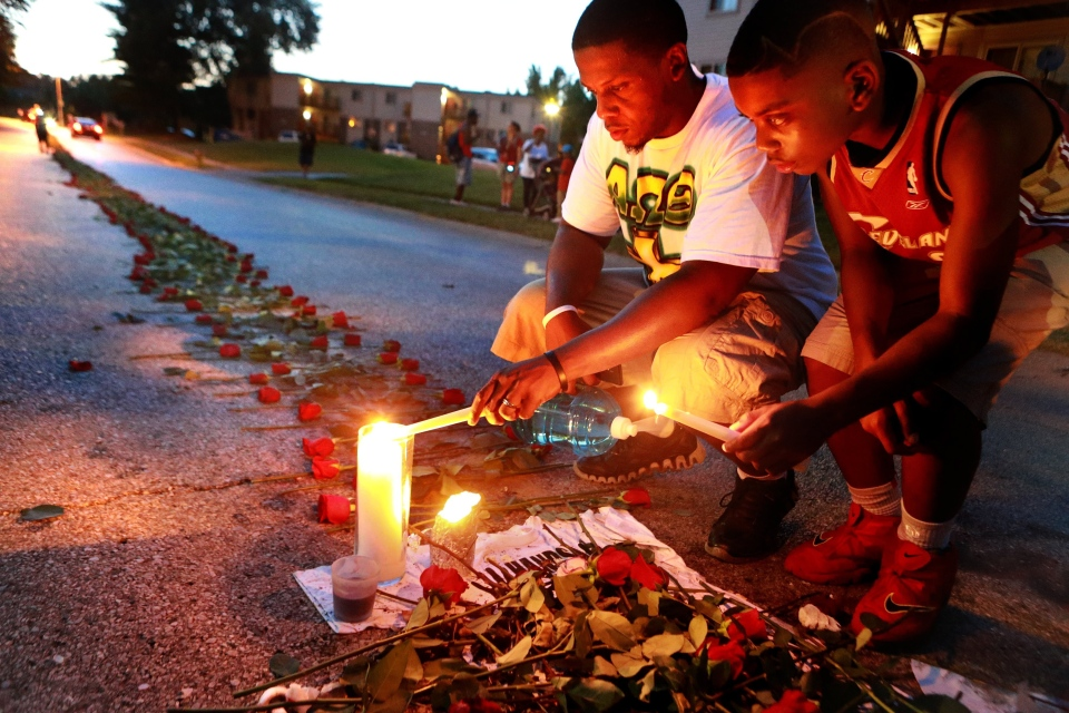Theo Murphy, left, of Florissant, Mo., and his brother Jordan Marshall, 11, light candles Thursday, Aug. 21, 2014 at a memorial on Canfield Drive in Ferguson, Mo., where where unarmed Michael Brown was fatally shot by Ferguson Police Officer Darren Wilson. (AP / St. Louis Post-Dispatch, Christian Gooden)