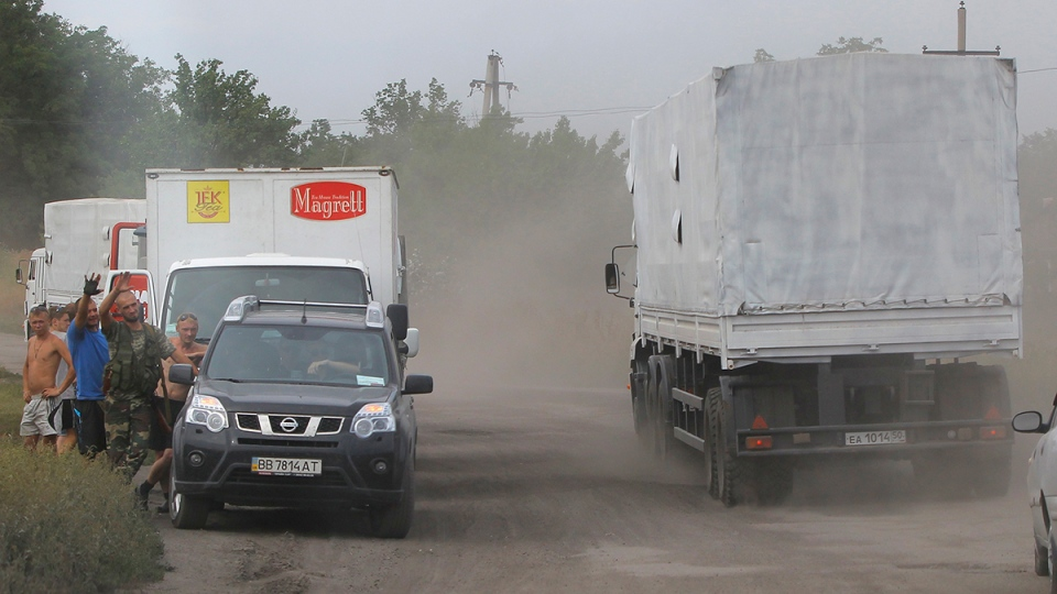 The trucks of a Russian aid convoy roll on the main road to Luhansk in the village of Bolshoi Sukhodol, after it passed the border post at Izvaryne, eastern Ukraine, Friday, Aug. 22, 2014. (AP / Sergei Grits)