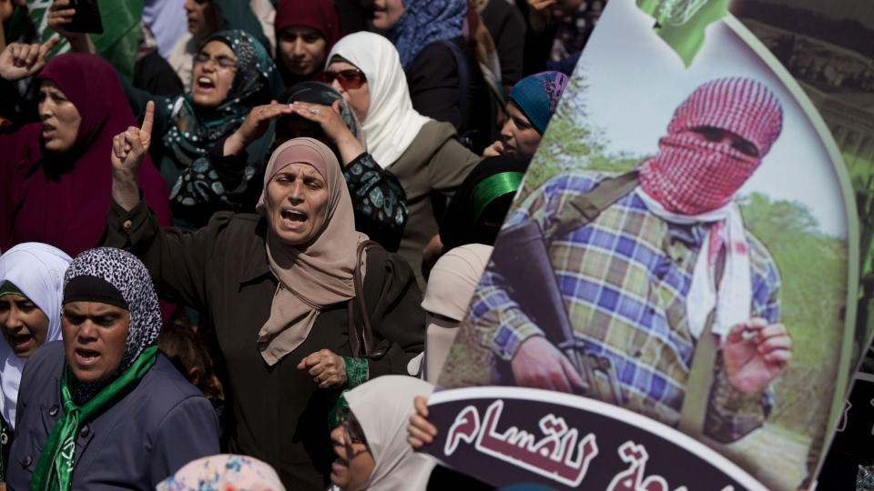 """A Palestinian supporter of Hamas holds a poster of its military wing, Izzedine al-Qassam Brigades, with Arabic writing that reads, """"Allegiance for al-Qassam,"""" as others shout slogans to protest against Israel and to support people in Gaza, during a demonstration in the West Bank city of Ramallah, Friday, Aug. 22, 2014. (AP / Majdi Mohammed)"""