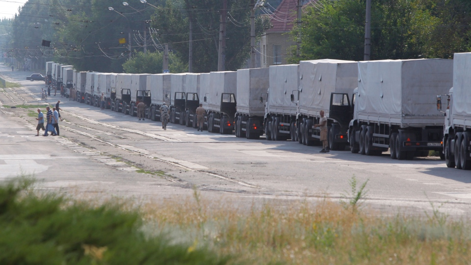 Drivers of the first trucks of the Russian aid convoy are parked in the city of Luhansk, easternUkraine, Friday, Aug. 22, 2014. (AP / Sergei Grits)